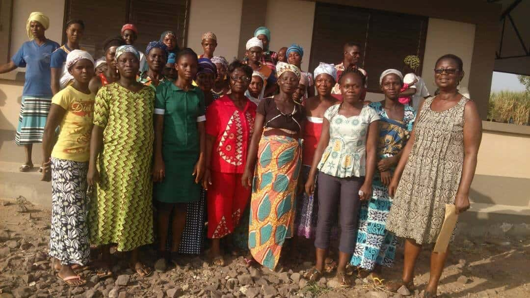 Public Health Nurse Elizabeth Sarfo Adu (in red) surrounded by ARC staff and villagers
